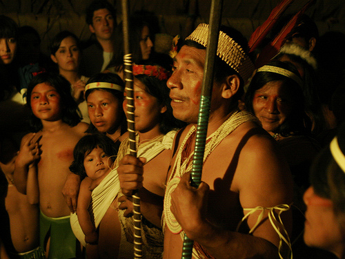 A Huaorani man armed with traditional spears and his wife and children welcome a group of tourists to the community of Tigüino, located within Yasuní National Park. Credit: Eduardo Valenzuela/IPS