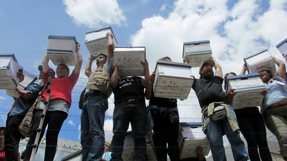 Lo logramos! Volunteers hold the boxes with signatures at the Electoral College